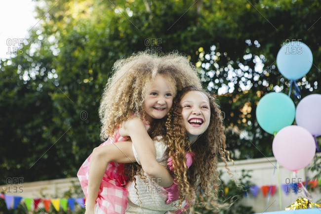 Girls giving piggyback rides at a birthday party | Stock