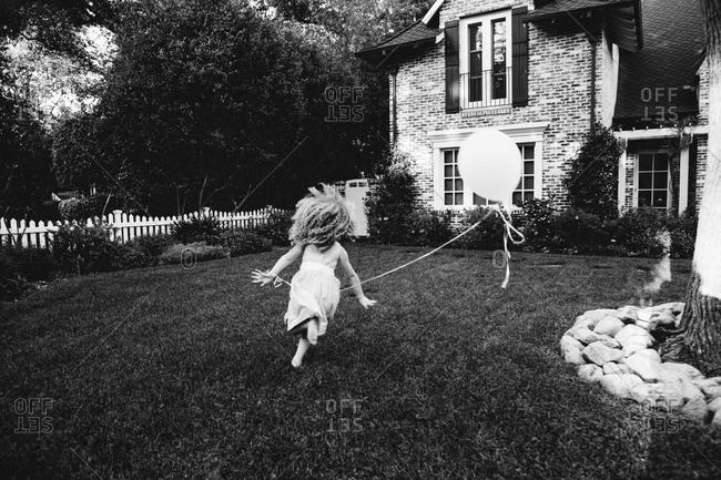 A girl runs with a balloon