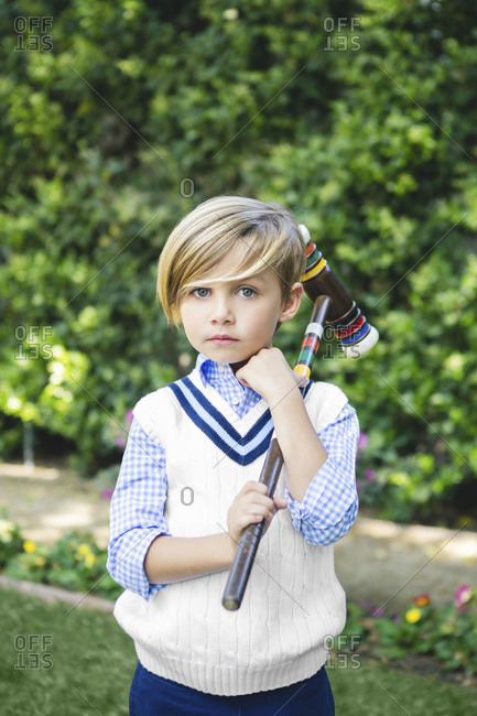 A boy takes a break from playing croquet