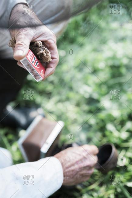 Beekeeper lighting a smoker with a match
