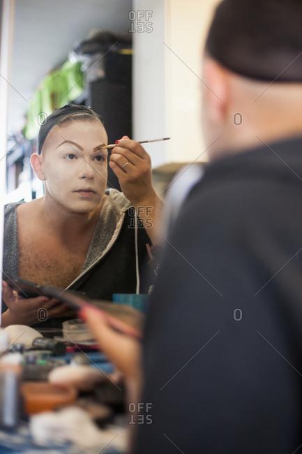 Man looking in mirror and applying drag makeup