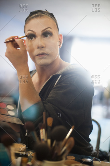 Man looking in mirror and putting on drag makeup