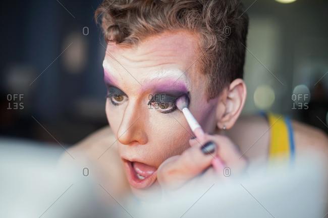Young man applying drag queen makeup
