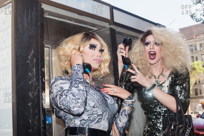 Two drag queens using a payphone