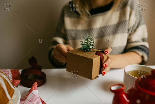 Woman wrapping gift box with pine and ribbon