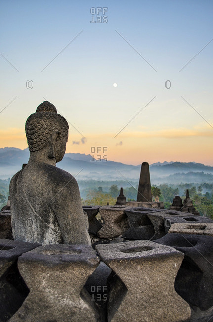 A Buddha statue overlooking the landscape at dawn from Borobudur Temple, Java