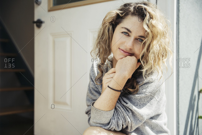 Casual young woman sitting outside by door
