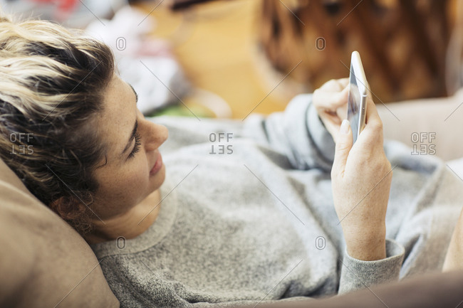 Woman lounging on her sofa with her phone