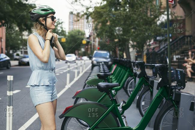 Woman putting on helmet by bike share