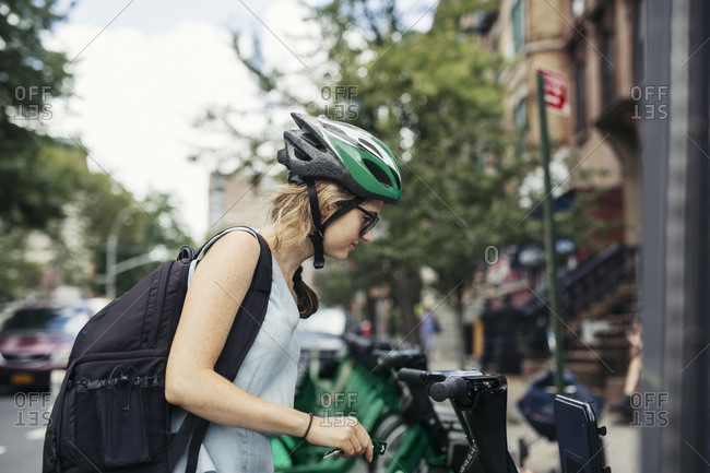 Woman selecting bicycle at bike share