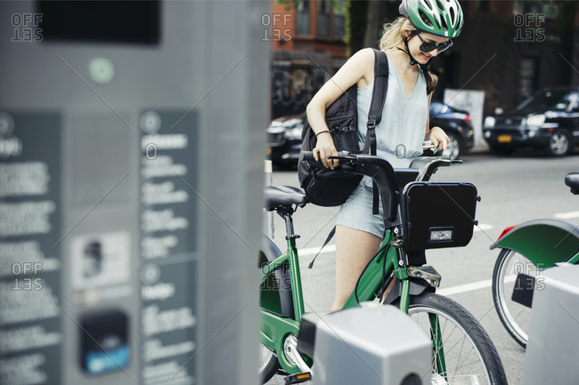 Woman standing with bike share bicycle
