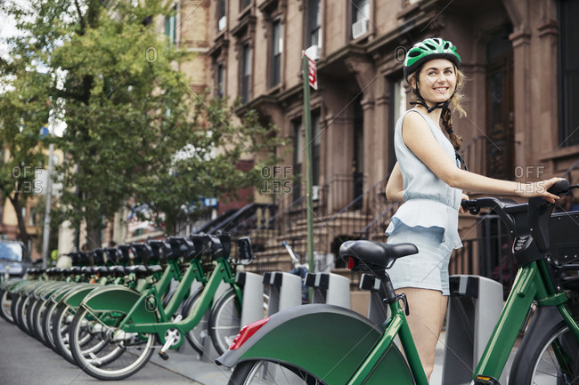 Woman smiling with bike share bicycle