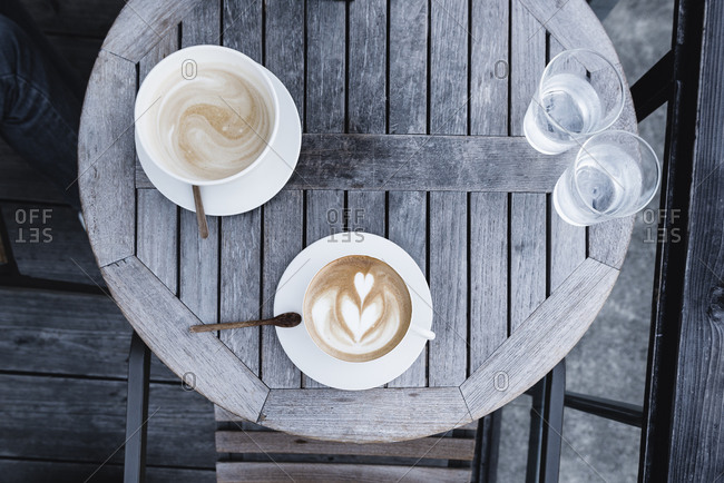 Two lattes on a wood table
