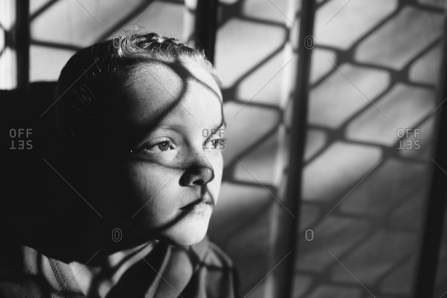 A young girl with the shadow of a chain-link fence on her face
