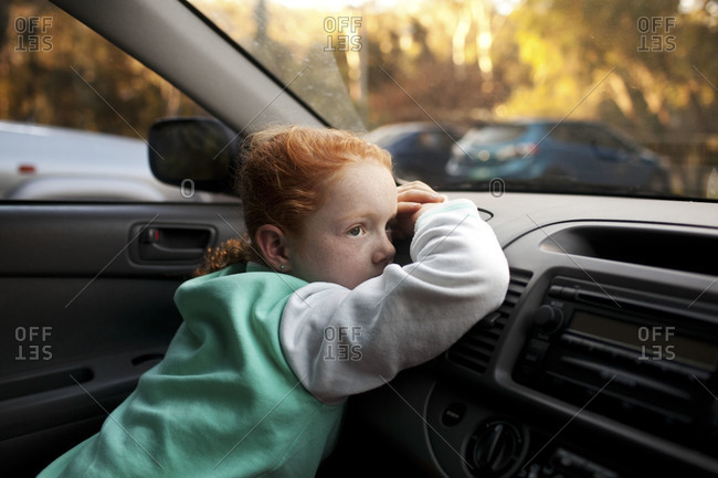 A girl leans against the dashboard of a car