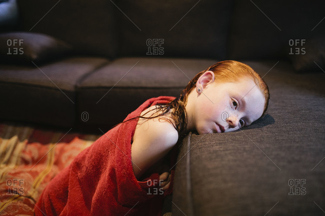 A girl lays  her head on her couch after a bath