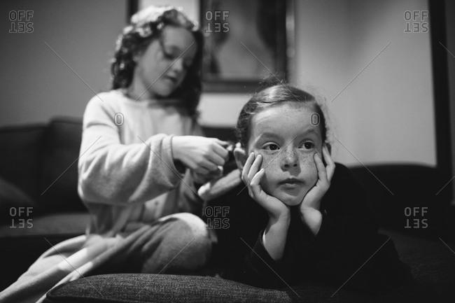 A girl braids her sister's hair