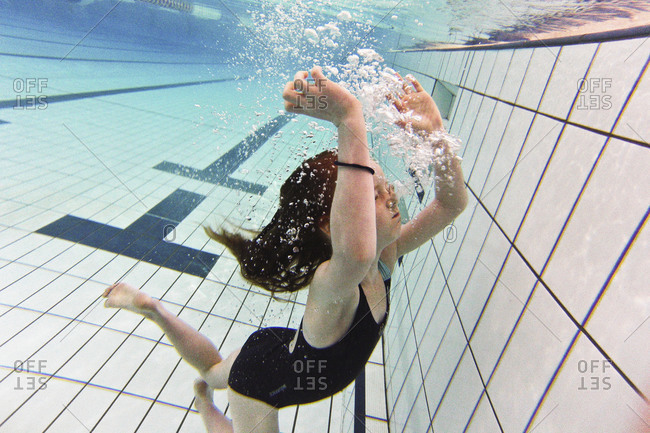 A girl blows bubble from her nose while swimming underwater