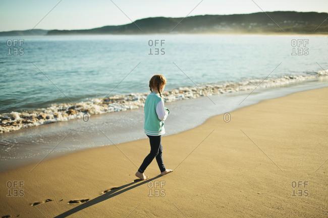 A girl walks along the sandy beach in a jacket
