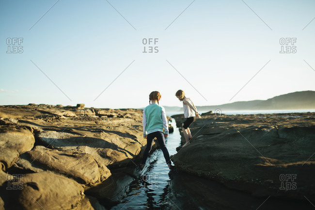 Sisters explore a tide pool at the shore