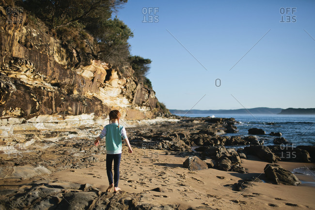 A girl walks along a rocky beach