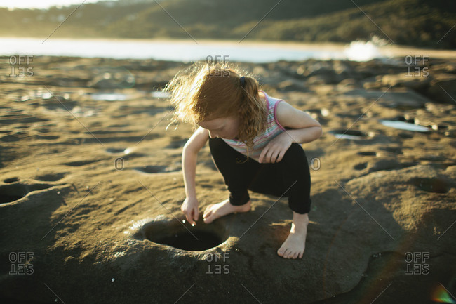 A girl looks in a hole at the shore