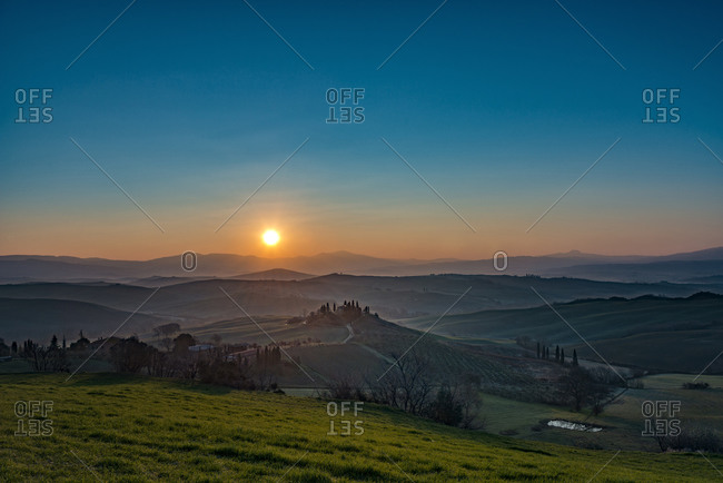 View of the rolling landscape of Val d'Orcia at sunrise