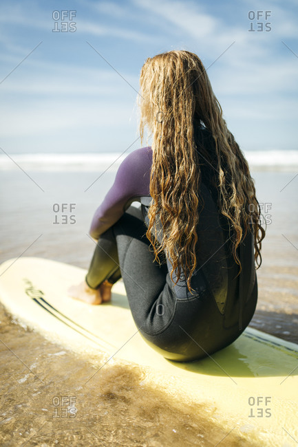 Back view of young woman sitting on surfboard on the beach