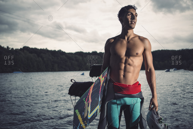 Young wakeboarder standing with his equipment at lakeshore