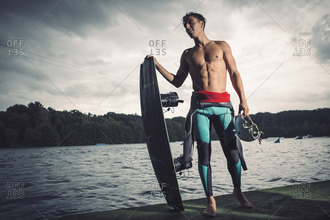 Young wakeboarder posing with his equipment at lakeshore