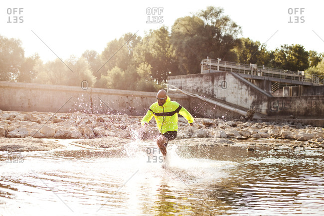 Man in sports wear running through water