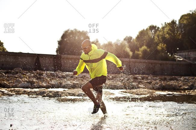 Man in sports wear running in water