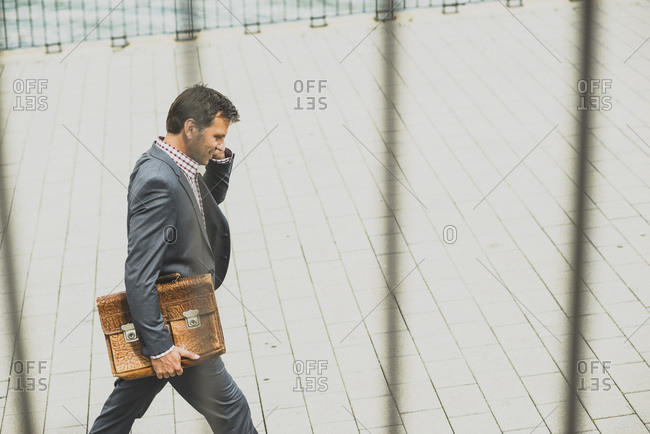 Businessman walking in the street and talking on the phone