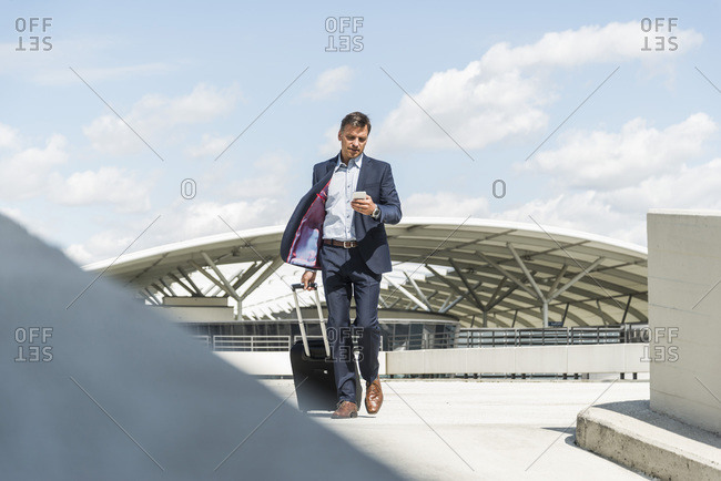 Businessman checking flight status on his cell