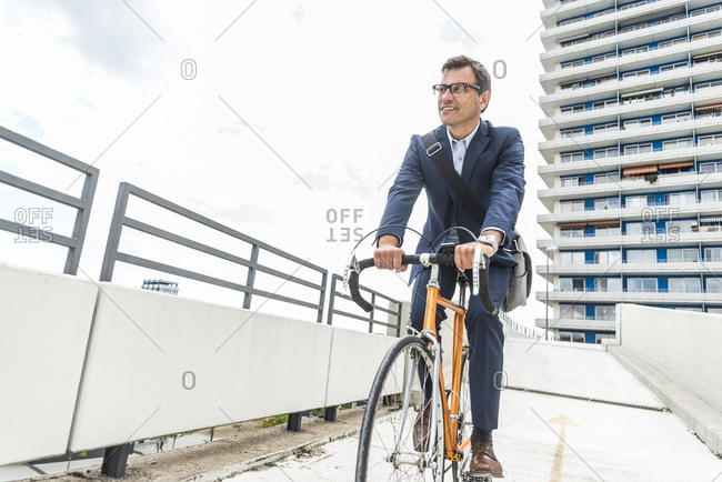 Businessman riding bicycle down a ramp