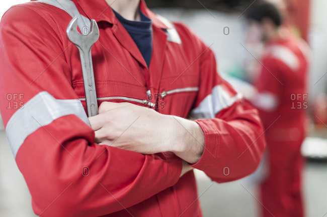 Car mechanic with folded arms and a wrench