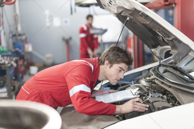 Car mechanic at working under the hood
