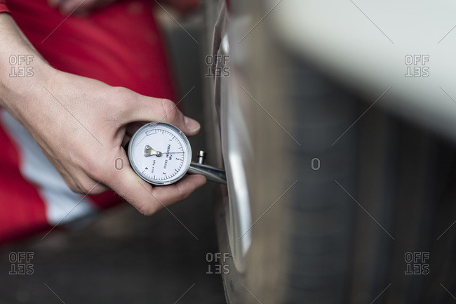 Car mechanic checking tire pressure gauge