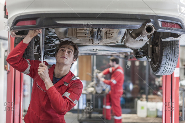 Car mechanic at working under a car