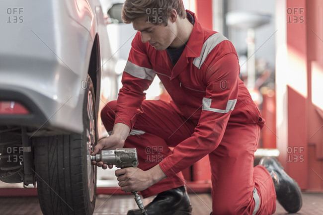 A mechanic changing a tire with impact driver
