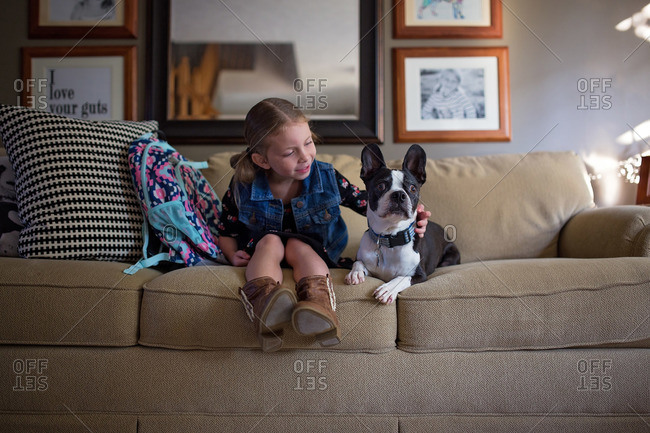 Girl sitting on couch with family dog