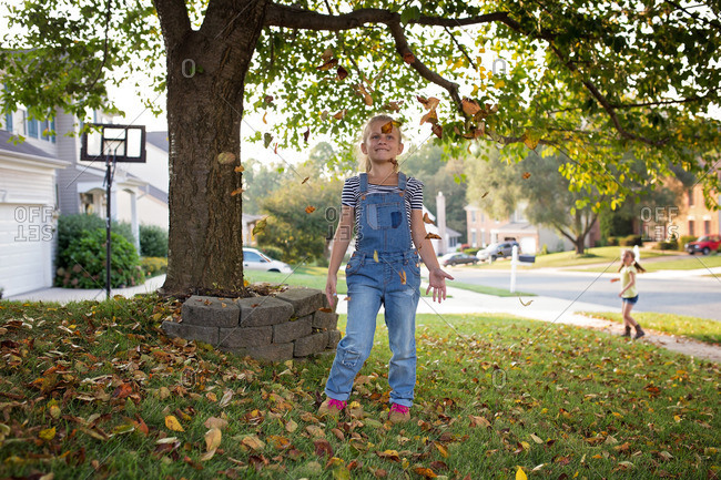 Girl in overalls throwing leaves