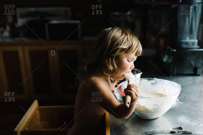 Little girl licking dough off spoon