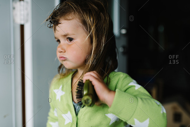 Young girl brushing her wet hair