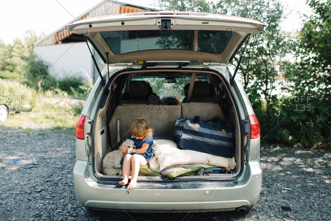 Little girl and dog sitting in back of van