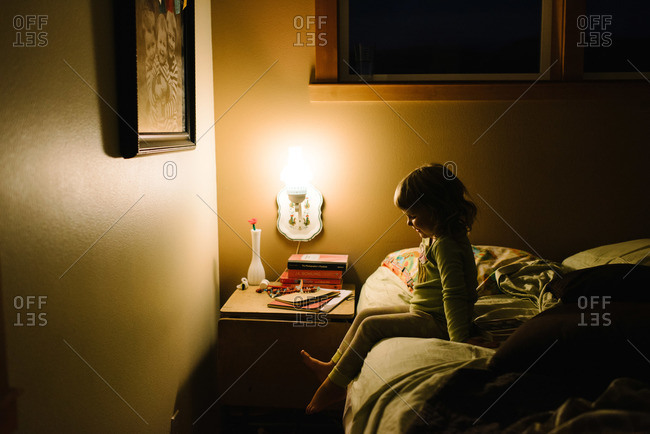 Young girl on side of bed at night