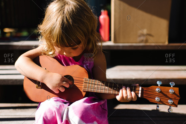 Little girl with a ukulele on steps