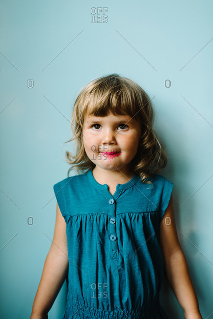 Girl with candy on lips against a wall