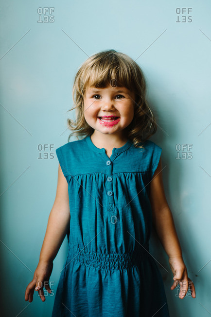 Smiling girl with candy on lips against wall