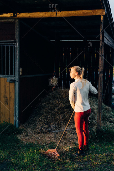 Woman raking hay into a horse stall